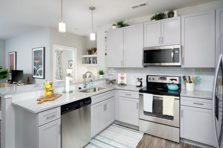 Open kitchen with built-in microwave and stainless steel appliances | The RED Apartments
